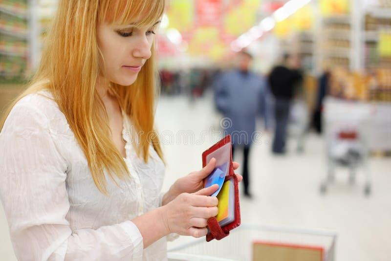 A menina loura começ o cartão de crédito da bolsa na loja fotos de stock royalty free