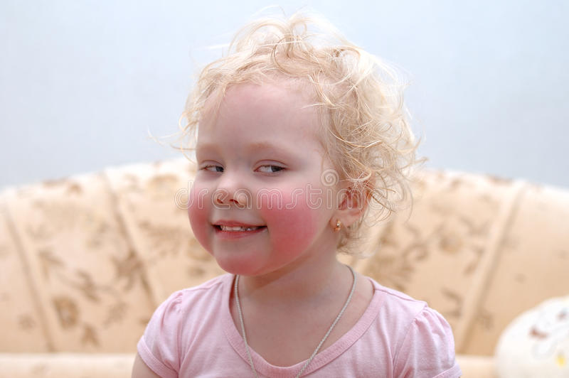 A menina loura consideravelmente curly faz as faces. foto de stock