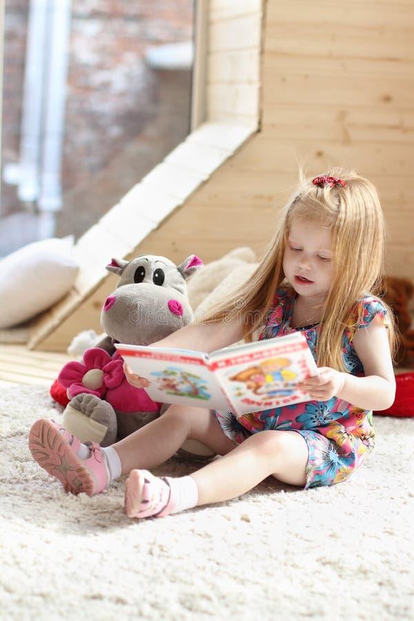 A menina loura consideravelmente pequena senta-se perto do brinquedo macio no tapete fotografia de stock royalty free