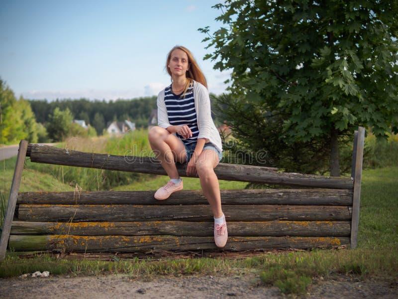 Menina loura da beleza que levanta na cerca de madeira velha foto de stock