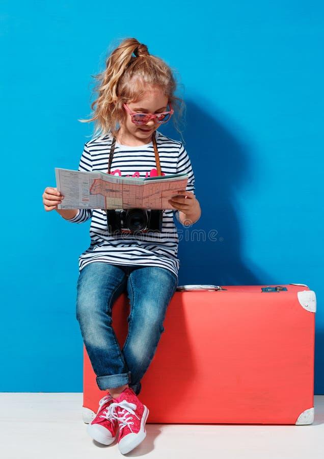 A menina loura da criança com a mala de viagem cor-de-rosa do vintage e a cidade traçam pronto para férias de verão Conceito do c fotos de stock royalty free