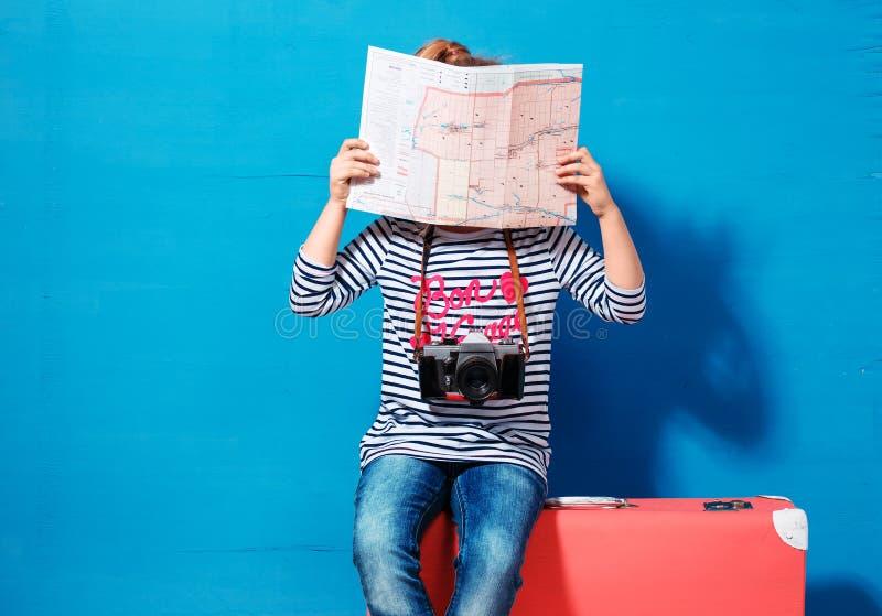 A menina loura da criança com a mala de viagem cor-de-rosa do vintage e a cidade traçam pronto para férias de verão Conceito do c foto de stock