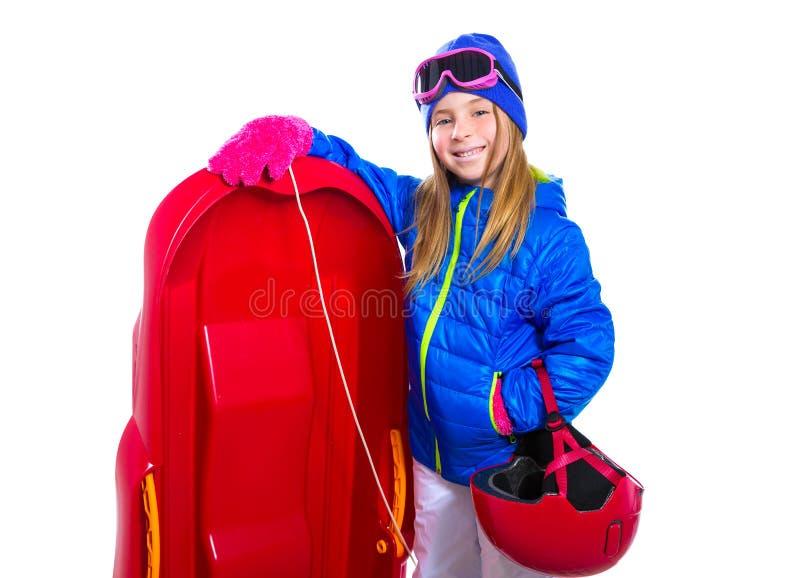 Menina loura da criança com o capacete e os óculos de proteção vermelhos do equipamento da neve do trenó foto de stock
