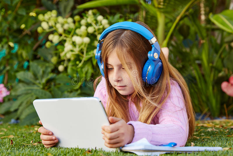 Menina loura da criança com o PC da tabuleta que encontra-se no relvado da grama imagens de stock royalty free