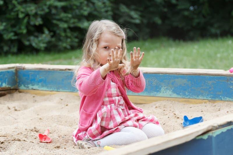 Menina loura da criança em idade pré-escolar virada que mostra lhe as palmas sujas fotos de stock