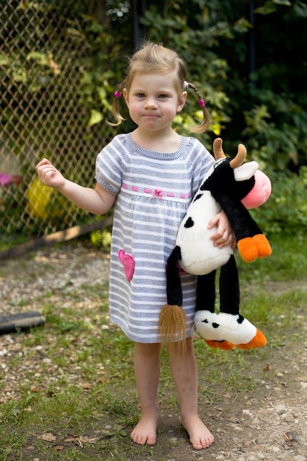 Menina loura da criança nos pés desencapados do vestido do verão com brinquedo da vaca fotos de stock royalty free