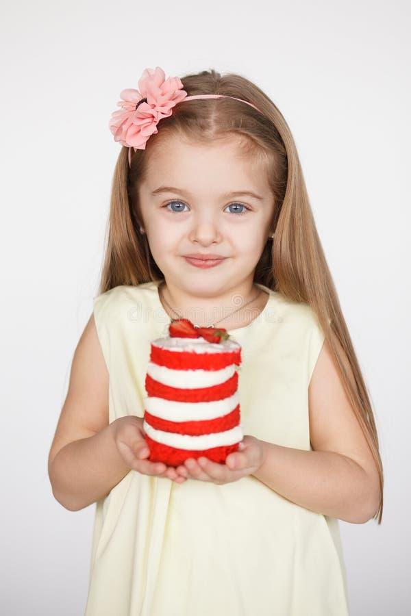 Menina loura da criança que guarda um bolo vermelho de veludo fotos de stock