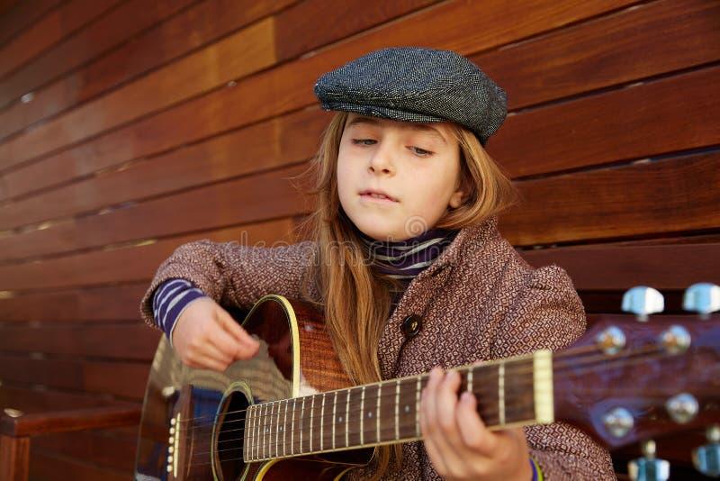 Menina loura da criança que joga a guitarra com boina do inverno foto de stock