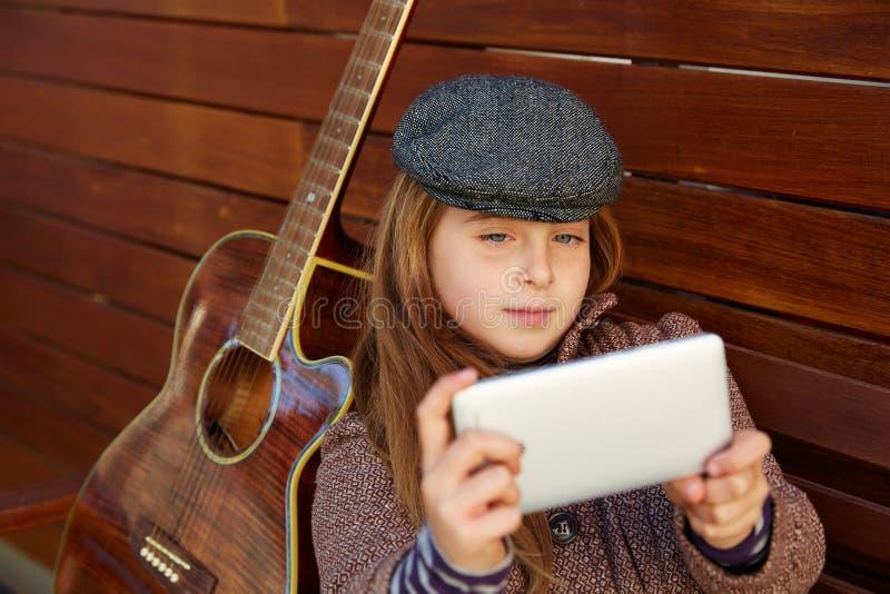 Menina loura da criança que toma a guitarra do selfie e a boina do inverno imagens de stock royalty free
