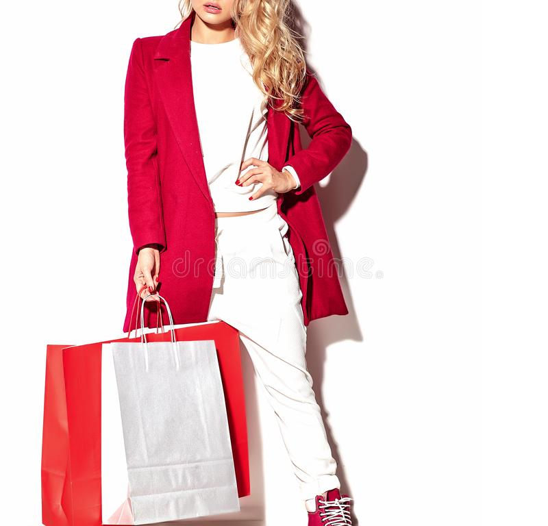 Menina loura da mulher que realiza em seu saco de compras grande das mãos na roupa vermelha do moderno isolada no branco imagem de stock royalty free