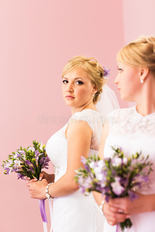 A menina loura da noiva bonita com composição brilhante branca do vestido e do penteado de casamento olha no espelho foto de stock royalty free