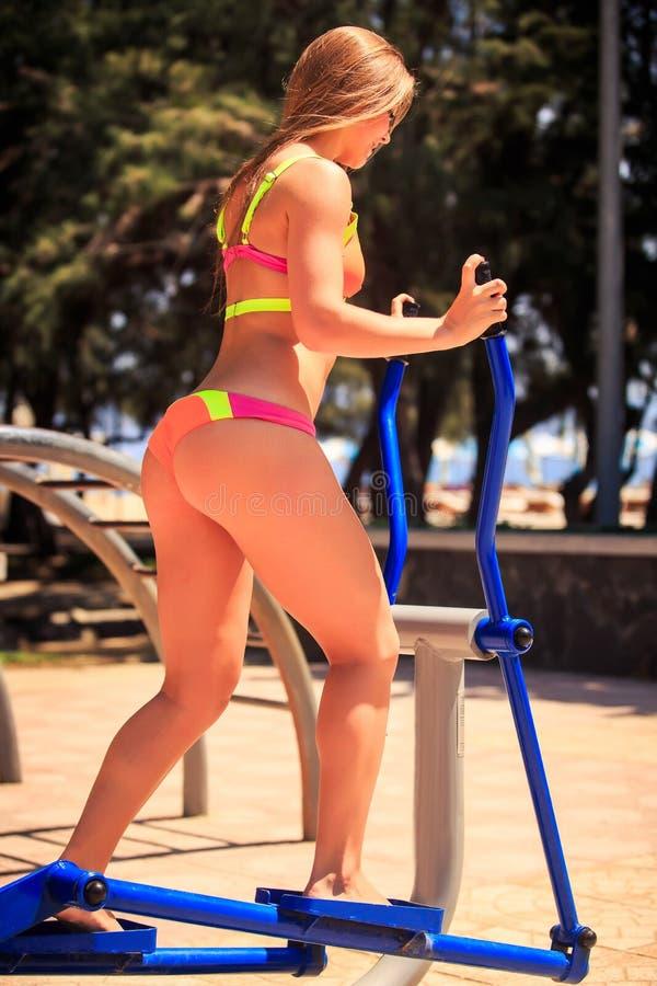 Menina loura da vista lateral no biquini em deslizante na terra de esporte imagem de stock