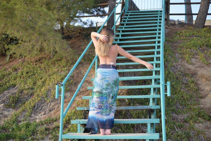 A menina loura dança em escadas de volta à câmera e abaixa seus braços fotografia de stock royalty free
