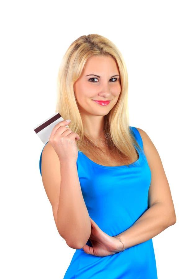 A menina loura de sorriso bonita atrativa nova no vestido azul guarda o cartão de crédito imagens de stock royalty free