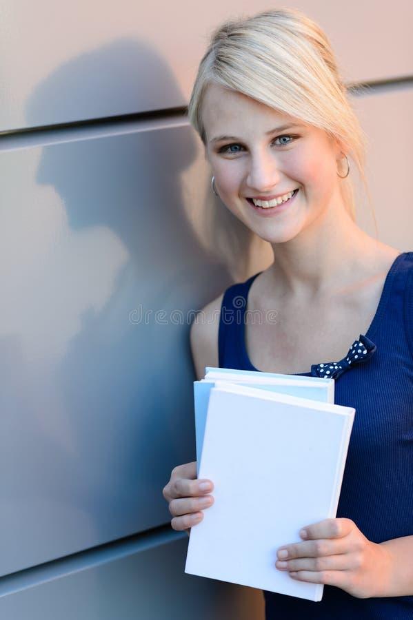 Menina loura de sorriso do estudante com livros fora imagens de stock