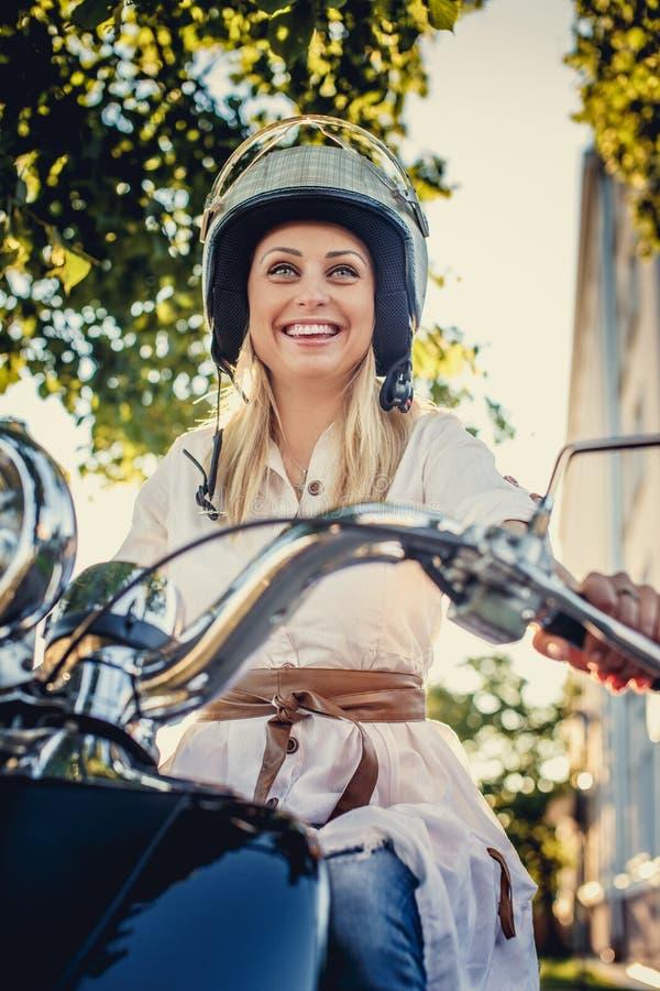 Menina loura de sorriso no helme do moto fotografia de stock royalty free