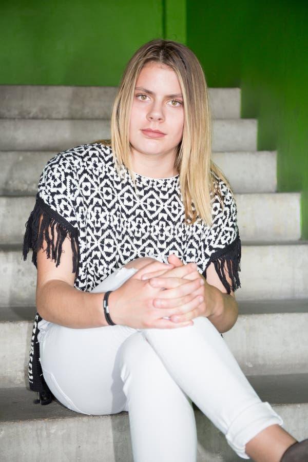a menina loura do adolescente bonito senta-se em escadas da rua imagens de stock royalty free