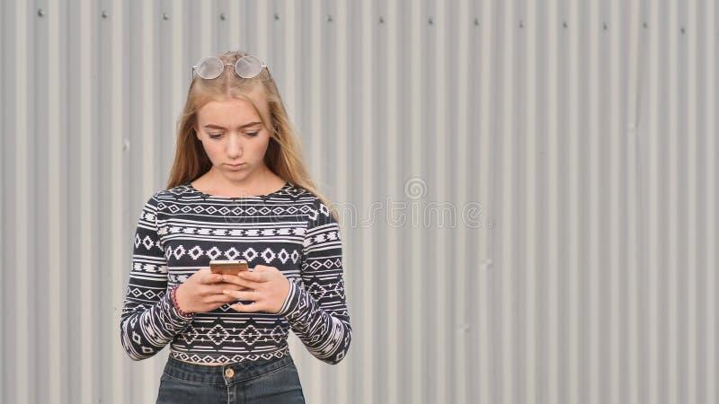 A menina loura do adolescente disca o número e no telefone e fala fotografia de stock