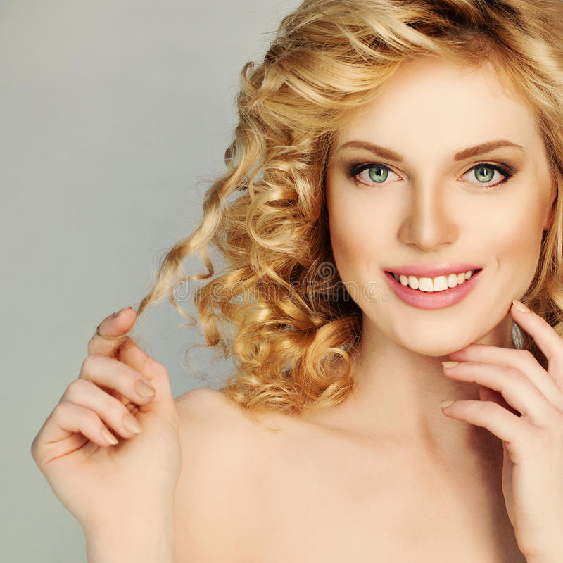 Menina loura do cabelo encaracolado A mulher de sorriso bonita toca em seu cabelo fotos de stock