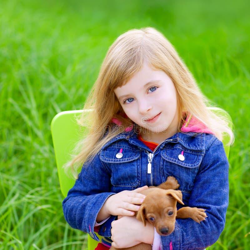 Menina loura do miúdo com o cão de animal de estimação do filhote de cachorro na grama verde fotos de stock royalty free