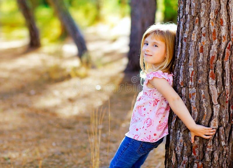 Menina loura do miúdo no tronco de árvore do outono fotografia de stock