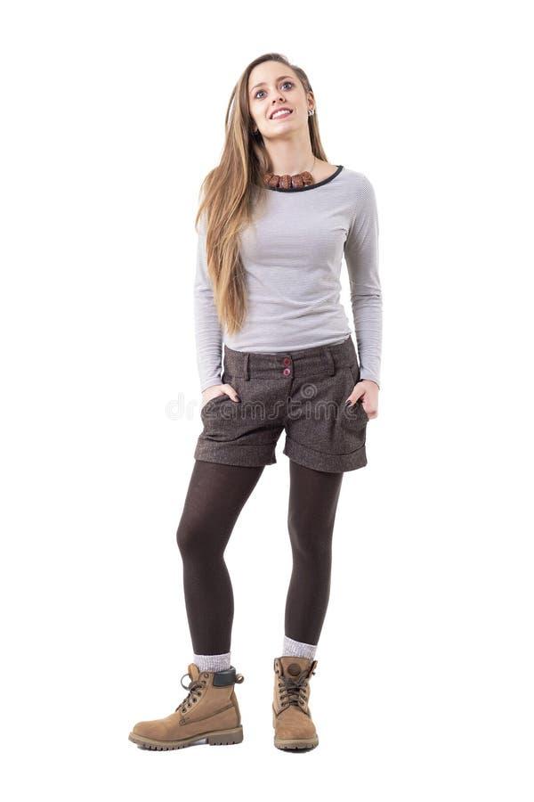 Menina loura do moderno do cabelo longo bonito relaxado que levanta com mãos em uns bolsos fotografia de stock royalty free