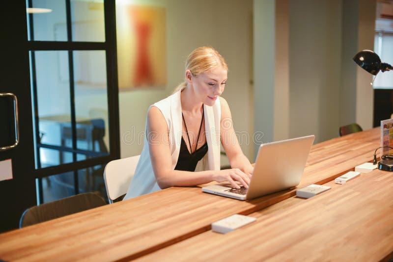 Menina loura do negócio que usa um portátil em um escritório imagem de stock royalty free