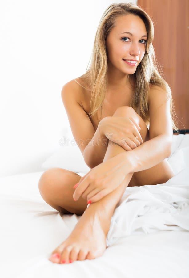 Menina loura do nude que senta-se na cama fotografia de stock royalty free