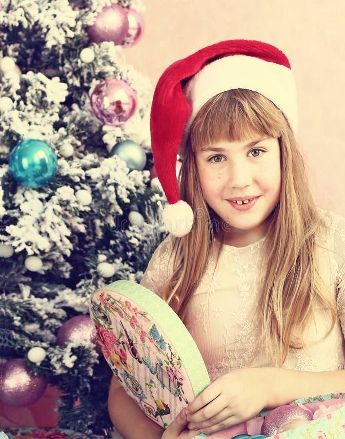 Menina loura do Preteen na caixa atual aberta do chapéu de Santa fotos de stock royalty free
