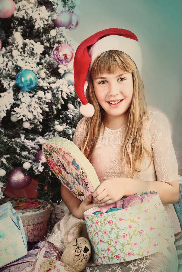 Menina loura do Preteen na caixa atual aberta do chapéu de Santa imagens de stock royalty free