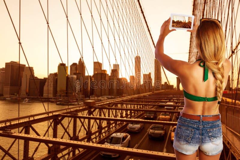 Menina loura do turista que toma a foto na ponte de Brooklyn fotos de stock