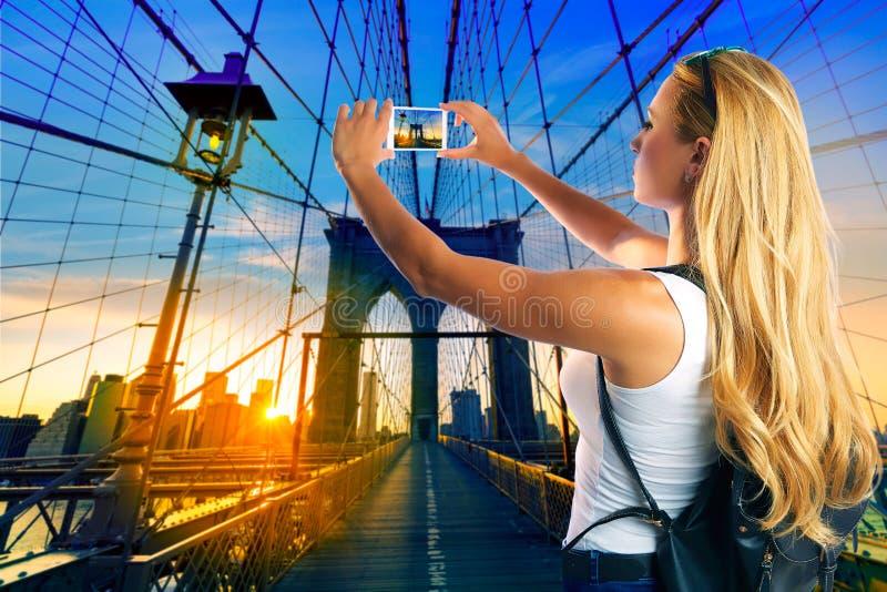 Menina loura do turista que toma a foto na ponte de Brooklyn fotografia de stock