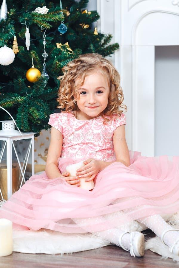 A menina loura doce com ondas em um vestido cor-de-rosa senta-se nas decorações do ano novo perto de uma árvore decorada com brin foto de stock