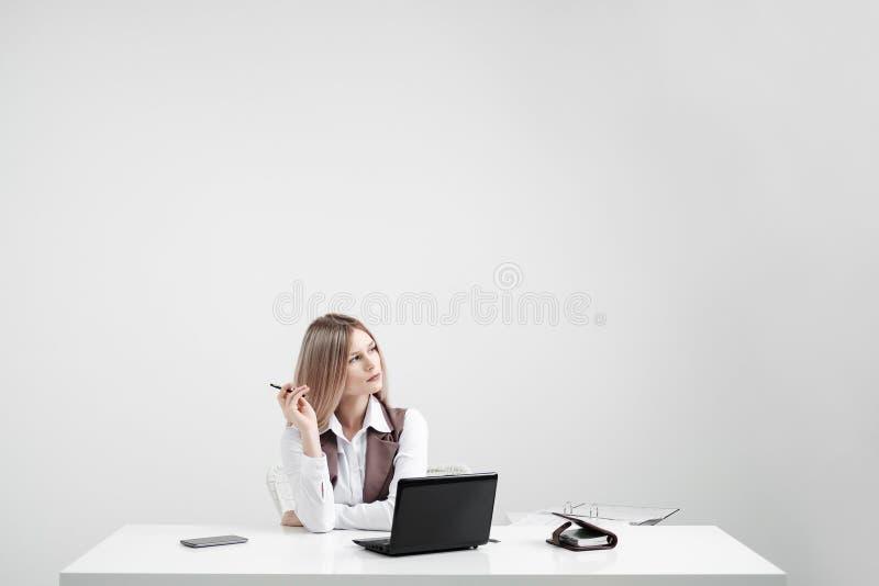 A menina loura em um terno de negócio trabalha em um computador em um escritório brilhante branco fotografia de stock