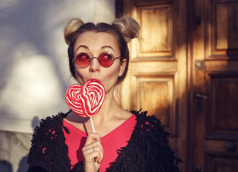 Menina loura em vidros cor-de-rosa que lambe um pirulito fotografia de stock