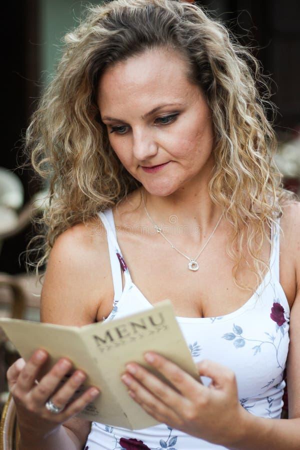 Menina loura encaracolado atrativa que senta-se em um café e em uma leitura homens fotos de stock