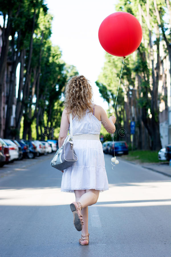 Menina loura encaracolado com baloon vermelho grande na rua fotografia de stock