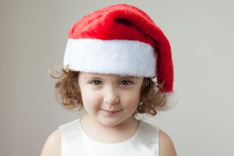 Menina loura encaracolado pequena engraçada em um chapéu de Santa fotos de stock royalty free