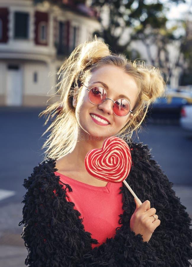 Menina loura engraçada nos vidros cor-de-rosa que guardam o lolliop foto de stock