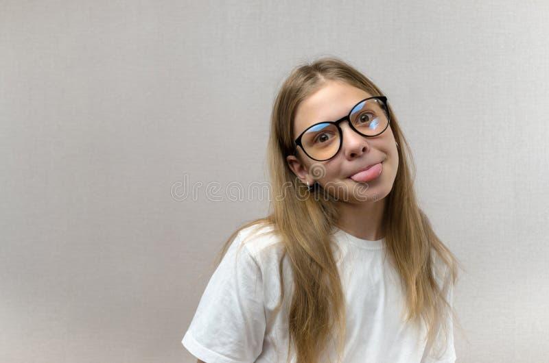 Menina loura engra?ada nos vidros que contorcem-se de dor sua cara, imitando, tendo o divertimento Close-up imagem de stock