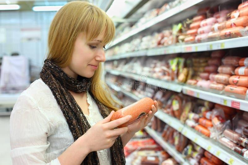 A menina loura escolhe a salsicha na loja fotos de stock