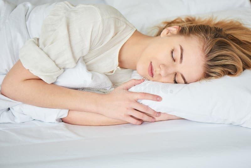 A menina loura está dormindo na cama branca imagem de stock