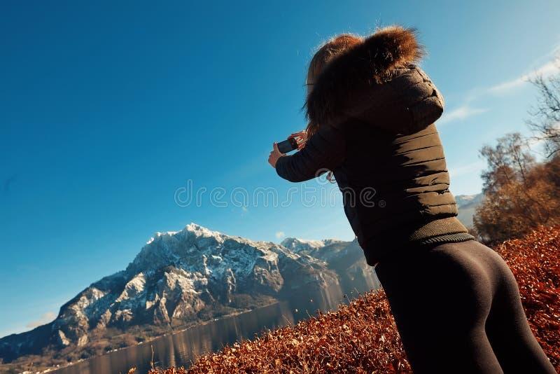 A menina loura está fazendo a imagem da montanha e do lago enormes na central de Europa pelo telefone imagens de stock royalty free