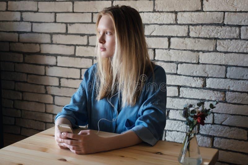 A menina loura está sentando-se com os fones de ouvido conectados ao telefone que está realizando nas mãos e está olhando de lado foto de stock