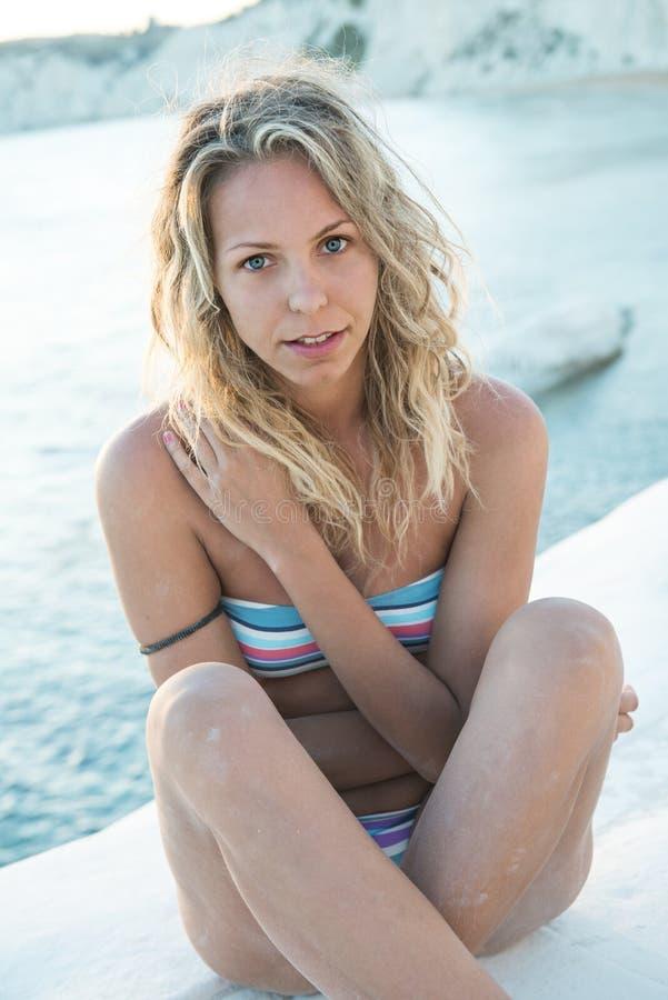 A menina loura está sentando-se em uma rocha branca pelo mar imagens de stock
