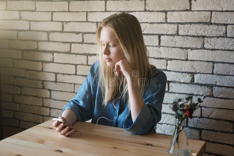 A menina loura está sentando-se nos fones de ouvido e olha no telefone que guarda o em uma mão, a outro está sustentando seu quei fotos de stock royalty free