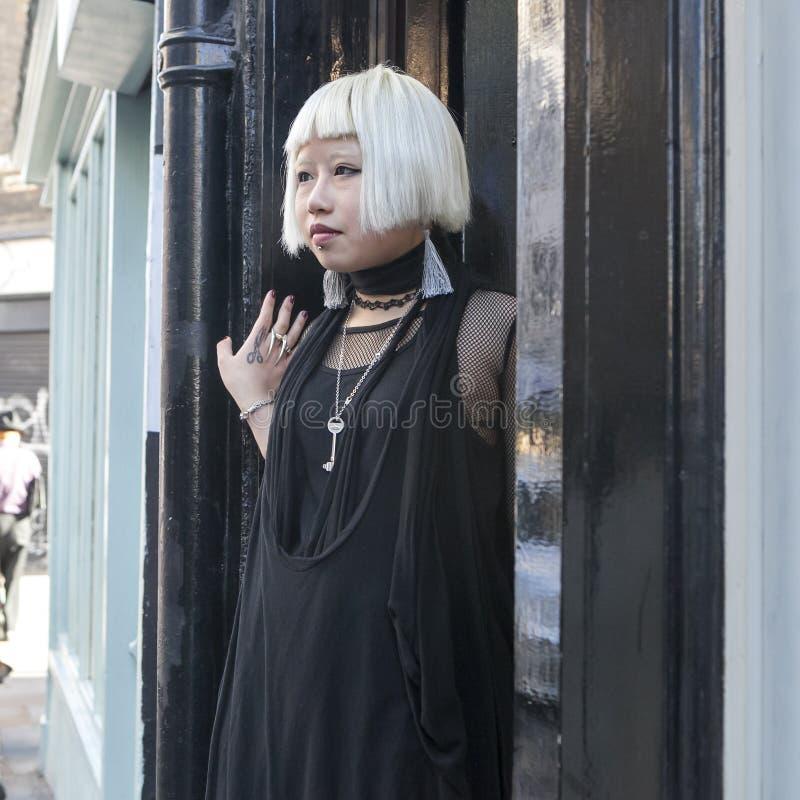 Menina loura Fashionably vestida nos óculos de sol em uma túnica preta que anda ao longo do Brickline imagem de stock