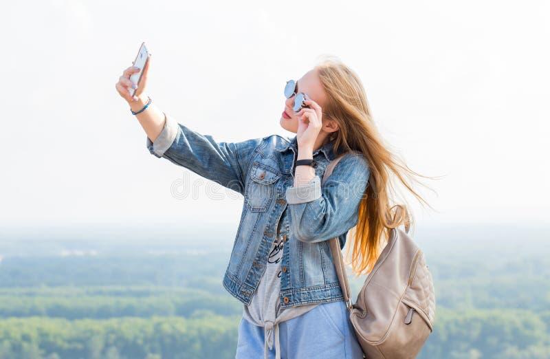 Menina loura feliz bonita que toma selfies fora no parque Retrato horizontal fotos de stock