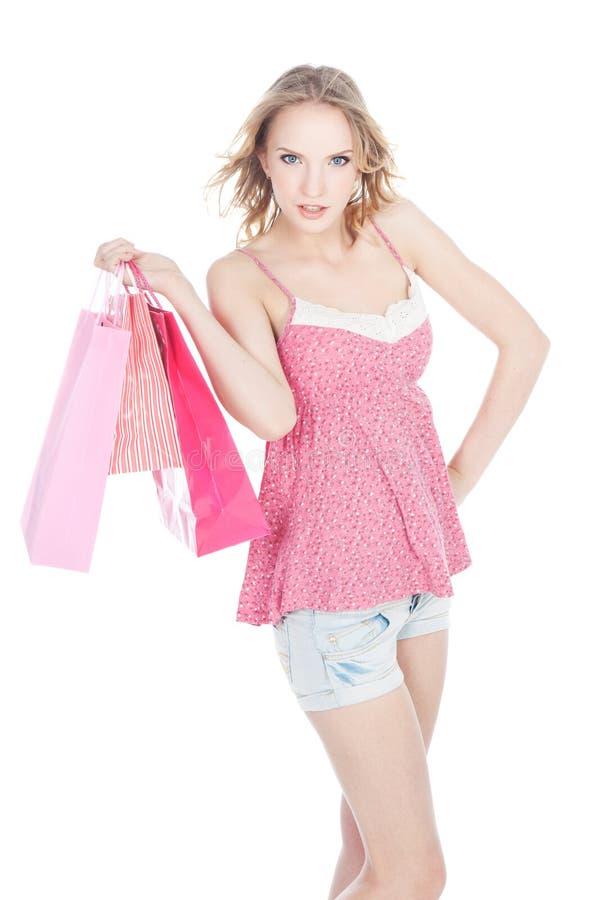 Menina loura feliz com os sacos de compra cor-de-rosa imagem de stock royalty free