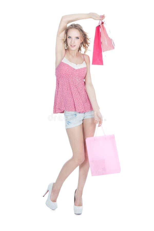Menina loura feliz com os sacos de compra cor-de-rosa fotografia de stock